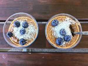 2 glasses filled with almond chocolate chia pudding topped with blueberries and coconut