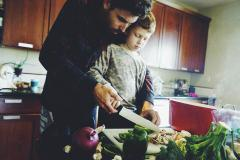 Man helping son in kitchen