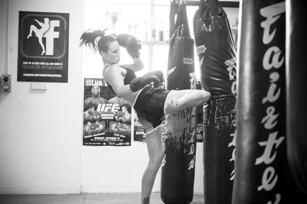 Woman kicking punch bag