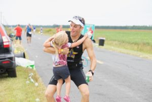 man carrying toddler at end of triathlon