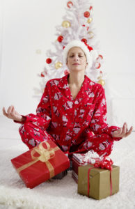 young female in christmas pajamas, meditating amongst the presents