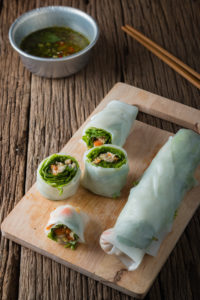 Fresh rice paper Rolls with vegetables on old wooden table